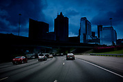 Cars and trucks drive on the highway under a bridge on their way to Atlanta. The faded windscreen gives a blue hue to the Atlanta skyline in the background.