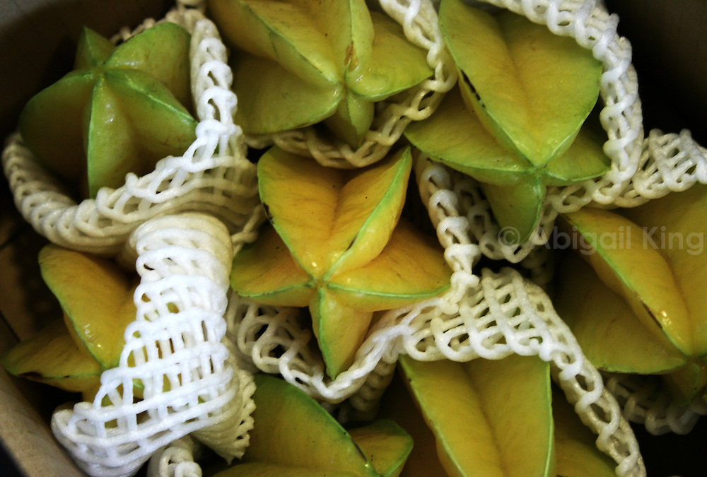 Starfruit in Okinawa, Japan, wrapped in white mesh and for sale in a market.