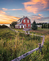 This scene seems to be made for painting. A little red cottage sits on the edge of the shore, with a split rail fence and well. Colorful weeds grow around the fence while the lawn close to the house is well manicured and landscaped. The sky above is painted with glowing orange clouds at sunset.