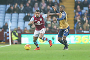 Aston Villa's Leandro Bacuna & Arsenal's Joel Campbell tussle for the ball during the Barclays Premier League match between Aston Villa and Arsenal at Villa Park, Birmingham, England on 13 December 2015. Photo by Shane Healey.