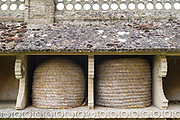 Niches or boles with straw bee skeps - early bee hives - at The Bee Shelter in Hartpury UK. 19th century old stone bee shelter, Grade II listed structure.