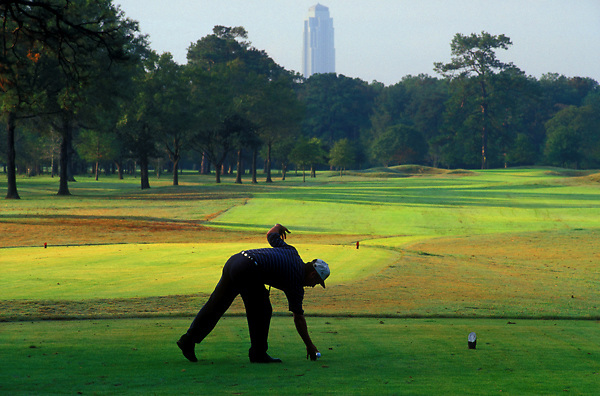 Stock photo of a man setting his golf ball to make the drive