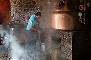 A worker operates the still which uses steam and pressure to extract alcohol from crushed blue agave fibers for tequila at the Casa Siete Leguas, El Centenario distillery in Atotonilco de Alto, Jalisco, Mexico. The Seven Leagues tequila distillery is one of the oldest family owned distilleries and produces handcrafted tequila using traditional methods.