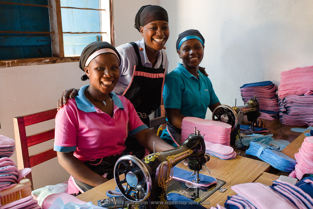 Annette Namale (left), Makula Hajarah and Bridget Nakuya at the Afripads factory in the village of Kitengeesa in the Central Region of Uganda on 30 July 2014.<br /> <br /> Started by volunteers in 2009, Afripads manufactures reusable fibre sanitary pads made locally by community residents. Beginning with a single employee, the company now employs roughly 100 women and produces approximately 700 kits (consisting of pads, holders and a bag) each week. At USh 12,000 to 15,0000 (&pound;2.75 to &pound;3.40) for a kit that lasts approximately one year, Afripads offer a significant saving over disposables which may cost in excess of USh 42,000 (&pound;9.60) over the course of a year. And for the many girls and women who cannot afford disposables, they offer an affordable and more hygienic alternative to rags, cotton wool or toilet paper, all of which are frequently used. At schools where Afripads have been distributed, teachers report that absenteeism has dropped sharply as girls who previously did not have access to proper sanitary pads now no longer stay home when they have their periods.