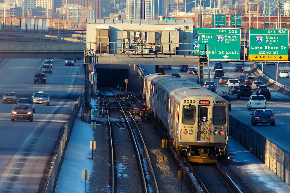 A Red Line L train is about to enter the underground tunnel after doing some 'between the interstate' running on the Dan Ryan expressway as rush hour commuter traffic on the parallel auto lanes begins to build.