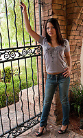 Young girl posing at an iron door in a mansion entrance.