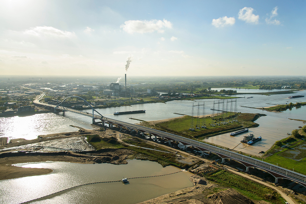 Nederland, Gelderland, Nijmegen, 24-10-2013; <br /> De nieuwe stadsbrug van Nijmegen, De Oversteek met zicht op de zuidoever. Grondwerkzaamheden voor de dijkteruglegging Lent (Ruimte voor de Rivier). De dijken worden landinwaarts verplaatst en er wordt een nevengeul voor rivier de Waal gegraven. Midden in beeld de rookpluimen van de energiecentrale Electrabel Nederland.<br /> The new city bridge of Nijmegen on the river Waal, De Oversteek (The Crossing). Groundworks for the Dike relocation of Lent (project Ruimte voor de Rivier: Room for the River). <br /> luchtfoto (toeslag op standaard tarieven);<br /> aerial photo (additional fee required);<br /> copyright foto/photo Siebe Swart.