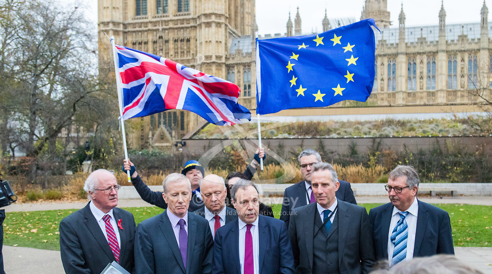 "London, December 05 2017. The DUP deputy leader Nigel Dodds flanked by other DUP MPs addresses the media, outlining the party's position relating to the Northern Ireland border in relation to the Brexit negotiations outside the House of Commons in London, as a pro EU campaigner disrupts proceedings by shouting ""Stop Brexit"" and waving a British and an EU flag. © Paul Davey"