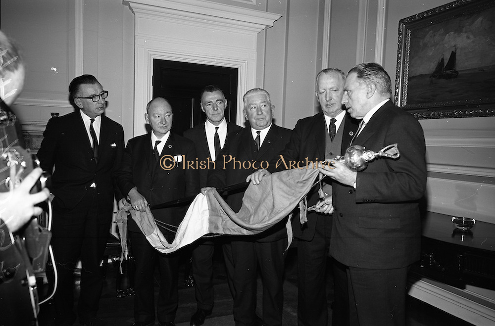 03/04/1966<br /> 04/03/1966<br /> 03 April 1966<br /> Taoiseach Sean Lemass presents staff and pennon for Liberty Hall. the tricolour pennon and band-master's staff were taken by a British officer from Liberty Hall during the 1916 Rising. A brother of the officer gave the items to Dr. Edward P. Carey of London in 1952 who presented them to Eamon de Valera who in turn presented them to the National Museum. Picture shows Mr. Lemass (right) handing over the staff and pennon to (from left) Mr. Fintan Kennedy, General Secretary, I.T.G.W.U.; Mr. Patrick O'Brien, National Trustee; Mr. Jack Brady, National Trustee; Mr. Edward Browne, Vice President and Mr. John Conroy, General President of the Union.