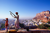 A father plays a musical instrument while his son sings and dances, with the Mehrangarh Fort and city of Jodhpur in the background, Rajasthan, India