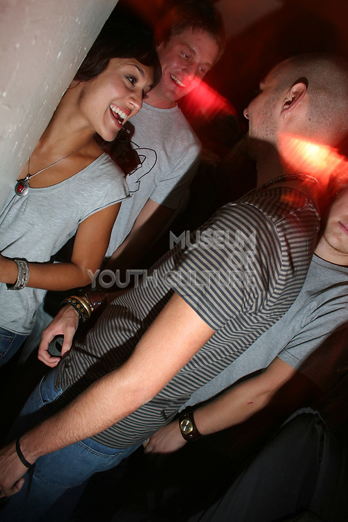 Girl laughing with friends, T Bar, London.