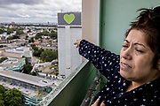 ENGLAND, London. Friday 14th June 2019. <br /> Former Grenfell Tower resident Georgina Agguire stands on her balcony with Grenfell Tower in the distance on the second anniversary of the tragedy in which 72 people were killed. Georgina had moved to Whitstable House, the building next door, four years prior to the fire.