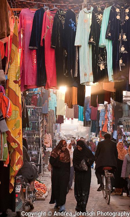 Muslim women walks past clothing stalls in ancient bazaar, Luxor, Egypt