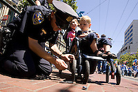 SAN FRANCISCO, CA - JUNE 24 : San Francisco police officer Lee Dahlberg fixes a wheel on the stroller of Jameson Callahan (2) and Camille d'Allance (4) during the 37th annual LBGT Pride Parade on June 24, 2007 in San Francisco, California. Hundreds of thousands of people lined the streets of San Francisco to watch and take part in the parade.  (Photograph by David Paul Morris)