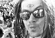 Man in sunglasses with painted eye symbol on forehead at the first Criminal Justice March, Trafalgar Square, London, UK, 1st of May 1994.