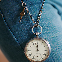 An old vintage pocket watch hanging from a persons jeans