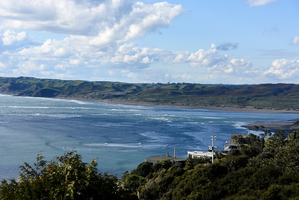 View from the hillside above Raglan surf area with waves and hills in the background