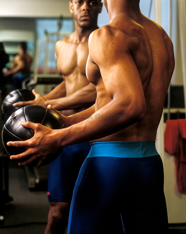 Athlete using a medicine ball to rehab from an injury.