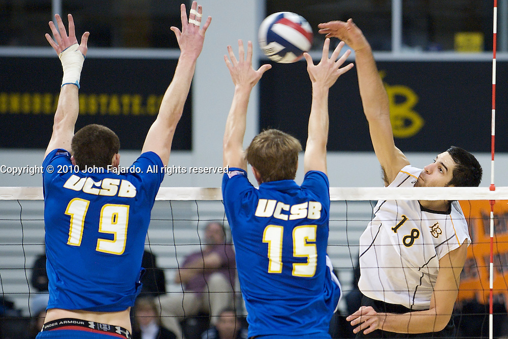 Dean Bittner(18) hits with Scott Slaughter(19) and Jake Rosener(15) blocking in the Big West Conference match against U.C. Santa Barbara at the Walter Pyramid, Long Beach CA, Friday Feb. 12, 2010.
