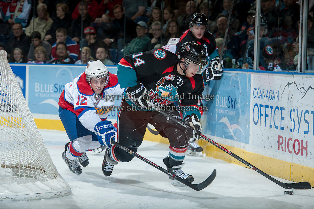 KELOWNA, CANADA - NOVEMBER 9: Rourke Chartier #14 of the Kelowna Rockets moves the puck behind the net as Cole Benson #12 of the Edmonton Oilers tries to stick check him on November 9, 2013 at Prospera Place in Kelowna, British Columbia, Canada.   (Photo by Marissa Baecker/Shoot the Breeze)  ***  Local Caption  ***