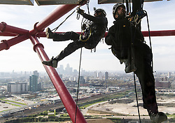 © Licensed to London News Pictures. 05/04/2014. Workmen precariously dangle 80 metres above East London as they prepare rigging for performing acrobats as part of the opening celebrations of the ArcelorMittal Orbit in Queen Elizabeth Park, Stratford. Photo credit : David Fearn/LNP