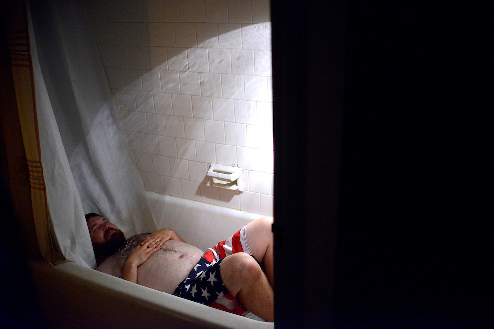 (photo by Matt Roth).Assignment ID: 30128227A..Lit by flashlight, Matt Fouse lays in the ice bath he prepared a little after midnight Sunday, July 1, 2012. His home, located on the 3200 block of Abell Ave in Baltimore, MD, is one of the millions left without power and air conditioning in the middle of a record breaking heatwave in the wake of the massive derecho storm which hit the Mid-Atlantic region Friday night. ...After the massive derecho storm Friday night, Matt Fouse lost power in his home on the 3200 block of Abell Ave in Baltimore, MD. Saturday night the nighttime temperatures dipped into the 90's outdoors.  ...After the deadly derecho storm swept through the Mid-Atlantic region Friday night, over three million in Maryland, Virginia, West Virginia, Ohio, and Washington D.C. are without power during a heat wave. In Maryland temperatures stayed in the 90's and 100's. .