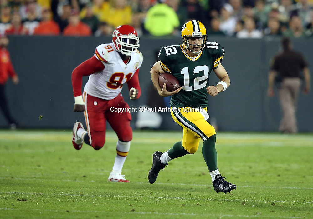 Green Bay Packers quarterback Aaron Rodgers (12) is chased by Kansas City Chiefs outside linebacker Tamba Hali (91) on an 11 yard run for a second quarter first down during the 2015 NFL week 3 regular season football game against the Kansas City Chiefs on Monday, Sept. 28, 2015 in Green Bay, Wis. The Packers won the game 38-28. (©Paul Anthony Spinelli)