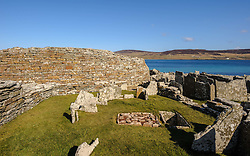 "The Broch of Gurness.  The Broch of Gurness is an Iron Age broch village on the northwest coast of Mainland Orkney in Scotland overlooking Eynhallow Sound. The remains of the central tower are up to 3.6 metres (11.8 ft) high, and the stone walls are up to 4.1 metres (13.5 ft) thick.The broch probably had a conical or mildly hyperbolic top,and has the remains of a settlement surrounding and adjoining it.<br /> <br /> Pieces of a Roman amphora dating to before 60 AD were found here, lending weight to the record that a ""King of Orkney"" submitted to Emperor Claudius at Colchester in 43 AD.<br /> <br /> The broch is in the care of Historic Scotland.<br /> <br /> (c) Andrew Wilson 