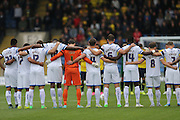 Wimbledon players observe a minutes silence during the Sky Bet League 2 match between Oxford United and AFC Wimbledon at the Kassam Stadium, Oxford, England on 10 October 2015.