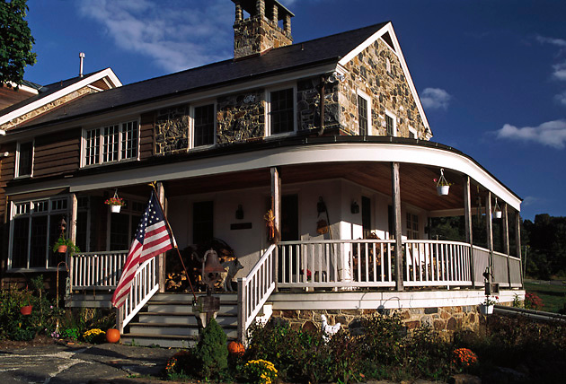 stone & wood house with wrap around porch, US flag