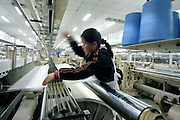 A worker adjusts threads on a loom at Standard Textile Factory in Linyi, Shandong Province March 30, 2005.