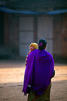 Mother carrying her child through Durbar Square in Bhaktapur, Kathmandu Valley, Nepal