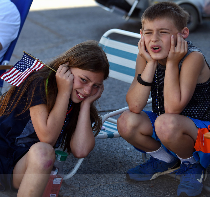 Sarah and Emerson Wilson cover their ears as colonial reenactors fire their muskets during Needham's annual Grand Parade on July 4, 2016.<br /> Wicked Local staff photo / Kate Flock