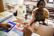 Counselor from UNICEF partner NGO Femme Active Cecile Traore, explains eMTCT medication to Marielle Gnabrayou Digbeto, 28, during a counseling session at the Koumassi general hospital in Abidjan Cote d'Ivoire on Friday July 19, 2013. Marielle is pregnant with her first child and HIV positive.