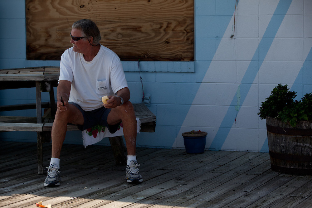 Billy Hill, of Atlantic Beach, N.C. sits on the porch of Triple S Marina during the calm after the wake of Hurricane Irene. Early projections of the storm predicted that the area would be in the  direct path of the hurricane, but the beach did not experience mass property damage. Residents are likely to remain without power until crews are able to repair feeds to the area.