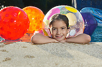 Girl in swimming pool with assortment of beach balls, portrait
