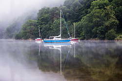 © Licensed to London News Pictures. 25/07/2017. Glenridding UK. Boats reflect in the still water of Ullswater Lake on a misty morning in the village of Glenridding in Cumbria this morning. Photo credit: Andrew McCaren/LNP