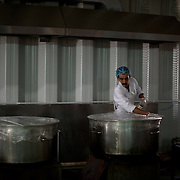 August 09, 2013 - Zarqa, Jordan: A syrian refugee works at the communal kitchen of Mrigb Al-Fuhud refugee camp, also known as Emirates-Jordanian camp, 20 kilometres east of the Jordanian city of Zarqa. Many refugees have been offered jobs inside the camp in a intent to bring some normality to their lives. At this kitchen, several meals are prepared daily to be distributed for free among all the camp's residents.<br /> The 10 million USD camp, which has 750 caravans, a hospital, and a school and can take up to four thousand people, first opened in April 2013 and was paid for by the United Arab Emirates. Work is underway to house a total of 20 thousand by the end of the year.<br /> In contrast with the two other camps in the area, Mrigb Al-Fuhud as been classified by many as a 'five star' camp due to impressive housing facilities provided to the refugees. (Paulo Nunes dos Santos/Al Jazeera)