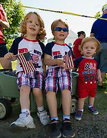 Parker, Preston and Pierson Ashton wave their American flags as they await the 4th of July parade Wednesday morning.  (Karen Bobotas/for the Laconia Daily Sun)