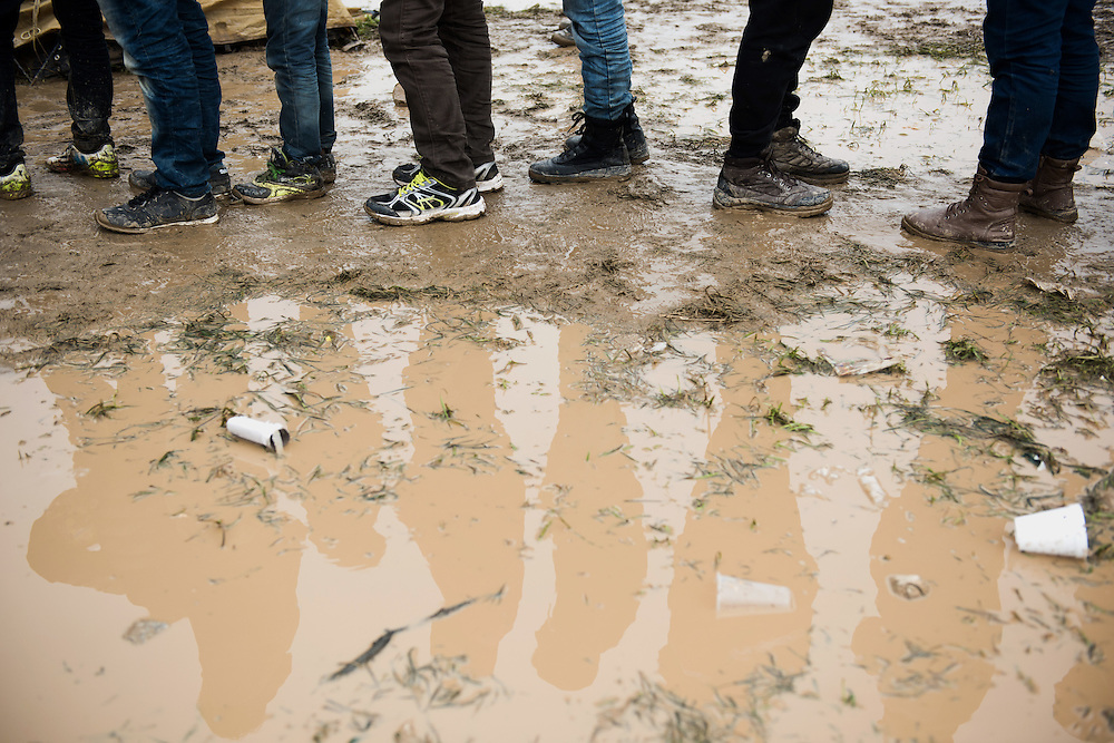 Refugees and migrants queuing in a muddy field for a cup of tea.  Transit camp of Idomeni, Greece. <br /> <br /> Thousands of refugees are stranded in Idomeni unable to cross the border. The facilities are stretched to the limit and the conditions are appalling.