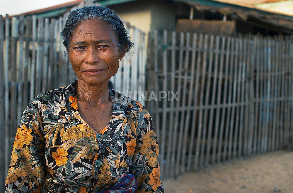 Old womman in front of traditional Bugis-style house, Papagaran island, Komodo National Park