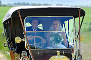 Bride and groom arriving at their wedding ceremony in a vintage car.