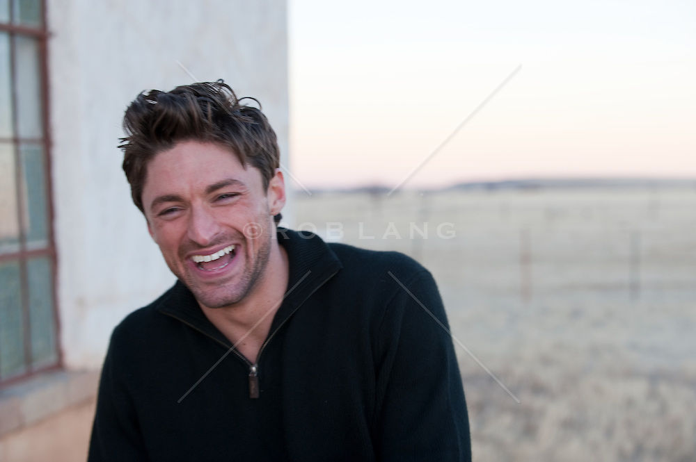 Man in a black sweater laughing near an adobe building in a field after sunset