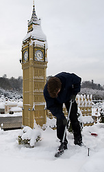 © under license to London News Pictures. 21/12/2010. A snow covered Lego London at Miniland, Legoland Windsor this morning (21/12/2010) following further snowfall last night. Pictured is model maker Joel brushing snow from the Houses of Parliament.. Photo credit should read: London News Pictures