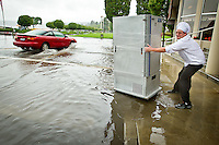 John Farmer, a kitchen supervisor at The Coeur d'Alene Resort, struggles to pull a cart of food up onto a flooded sidewalk along Front Avenue following a heavy rain storm Friday. The storm water system was quickly brought overcapacity as the downpour surged through drains and gutters.