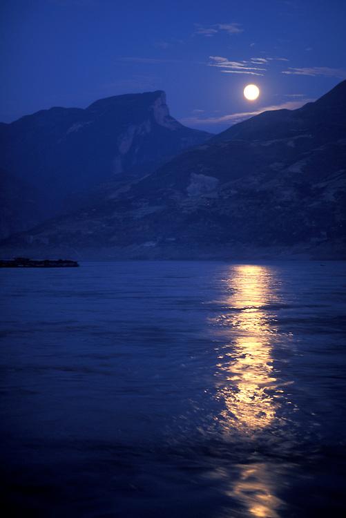 China, Sichuan Province, Fengjie, Full moon rises above hills along Yangtze River at dusk on autumn evening