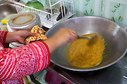 Iin Hartini cooking in her kitchen.<br /> <br /> In 2007 Iin started her own business selling Nasi Goreng (fried rice). <br /> <br /> She makes it in bulk for the school canteen to sell to children who have their breakfast at school. <br /> <br /> Prior to signing up to Usaha Wanita Iin had been beginning to feel demotivated about her work and for a short time ceased making the rice. Since receiving the advice and mentoring she has become reenergised for her business and her profits have tripled.