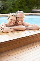 Middle-aged couple standing in pool at edge portrait