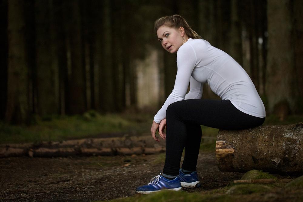 Model released - Kvinde sidder på træstamme og holder pause efter træning i skoven