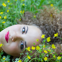 Young Girl staring at the viewer while lying in the grass with flowers
